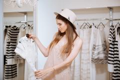 Pensive young woman choosing and looking at dress in showroom - stock photo