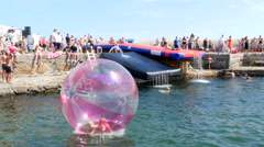 The girl is trying to stand up inside the big ball on the water surface Stock Footage