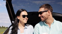 Happy couple with coffee at hatchback car trunk Stock Footage