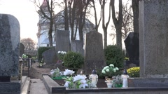Candles burn between grave stones in cemetery and church in small town. 4K Stock Footage