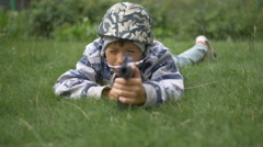 Child in camoflauge playing war shoots a toy gun Stock Footage