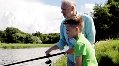 Grandfather and grandson fishing on river berth Stock Footage