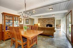 House interior with open floor plan. Dining room with wooden furniture set, l Stock Photos