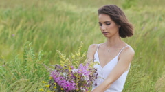 One young woman sitting on green field with flower bunch Stock Footage