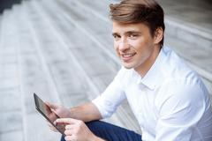 Portrait of happy businessman using tablet outdoors - stock photo