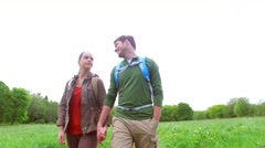 happy couple with backpacks walk on country road - stock footage