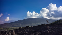 Landscape with clouds moving above black lava flow and volcano, 4K time lapse Stock Footage
