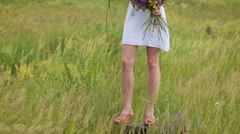 One young woman standing on green field with flower bunch Stock Footage