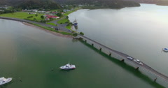 aerial over an old sailing ship and bridge in Paihia, New Zealand - stock footage