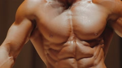 Strong masculine torso of professional bodybuilder posing at physique contest - stock footage