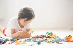 Cute little preschool child, boy, playing at home with constructor blocks, bu Stock Photos