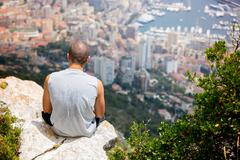 Young man on a hill above Monaco, contemplating the view Kuvituskuvat