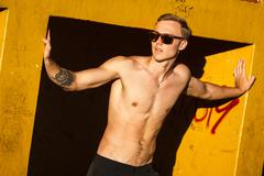 Young fit shirtless man exercising on outdoor sports ground Stock Photos