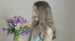 Beautiful happy girl enjoys bouquet flowers of irises and alstroemeria Stock Footage