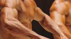 Male bodybuilder posing to show massive chest and biceps muscles at contest Stock Footage