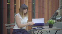 Businesswoman is browsing data in the folder, sitting on chair, outdoor. Steady. Stock Footage