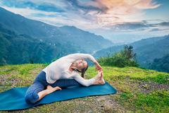Young sporty fit woman doing Hatha Yoga asana in mountains Stock Photos