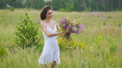 One young woman making a flower bunch standing on green field Stock Footage