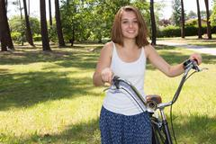 Portrait of Attractive Young Woman in blue shirt with cool beach cruiser Stock Photos