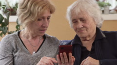 Patient daughter explains to her old mother how to use smartphone Stock Footage