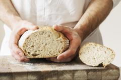 Baker holding a freshly baked loaf of bread. Stock Photos