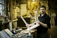 A man working in a furniture maker's workshop. Windsor chairs. Stock Photos