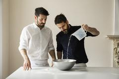 Two bakers standing at a table, preparing bread dough Stock Photos