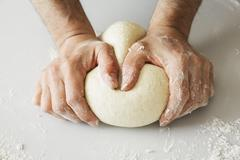 Close up of a baker kneading and shaping bread dough into a ball. Stock Photos