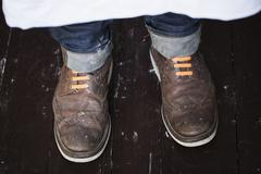 Close up of a man's feet, wearing brown shoes with orange shoe laces. Stock Photos