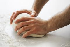 Close up of a baker kneading and shaping a portion of bread dough into a ball Stock Photos