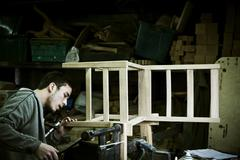 A man working in a furniture maker's workshop assembling a chair. Stock Photos