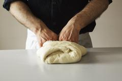 Close up of a baker kneading bread dough. Stock Photos