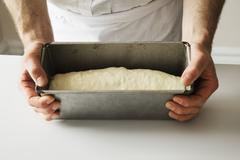 Close up of a baker holding a baking tin filled with bread dough. Stock Photos