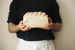 Close up of a baker holding a freshly baked loaf of white bread. Kuvituskuvat