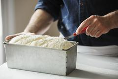 Close up of a baker cutting bread dough in a baking tin. Stock Photos