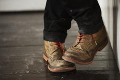 Close up of a man's feet, wearing brown brogues with red shoe laces. Stock Photos