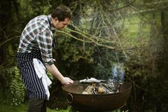 Chef standing in a garden, grilling a fish on a barbecue. Stock Photos