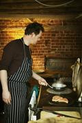 A man in a blue and white striped apron cooking fish on a hot plate on a stov Stock Photos