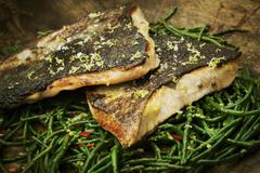 Close up of grilled fish fillets with crispy skin on a bed of samphire. Kuvituskuvat