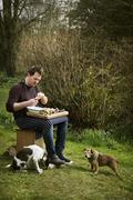 Chef sitting outdoors, preparing seafood, two dogs at his feet. Stock Photos
