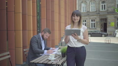 Businesswoman browsing tablet and smiles to camera. Outdoor. Steadicam shot. Stock Footage