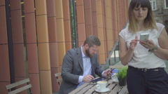 Businessman taking notes from smarthone to tablet, outdoor. Steadicam shot. Stock Footage
