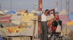 Barber shaving pilgrim at tent camp,Allahabad,Kumbh Mela,India Stock Footage