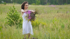 One young woman winding a flower bunch standing on green field Stock Footage