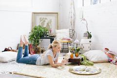 A woman in a light airy apartment relaxing, lying on the floor reading a book Stock Photos