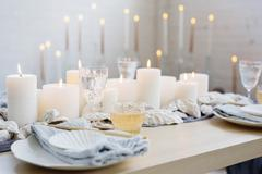 A table with lit candles, china plates and glasses. Stock Photos
