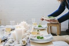 A woman placing a plate of food on a table decorated with lighted candles. Stock Photos