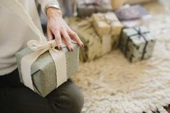 A woman sitting with a pile of wrapped presents. Stock Photos