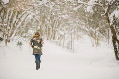 A woman walking in the snow in woodland. Stock Photos
