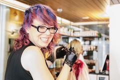 Hair colourist in gloves applying red hair dye Stock Photos